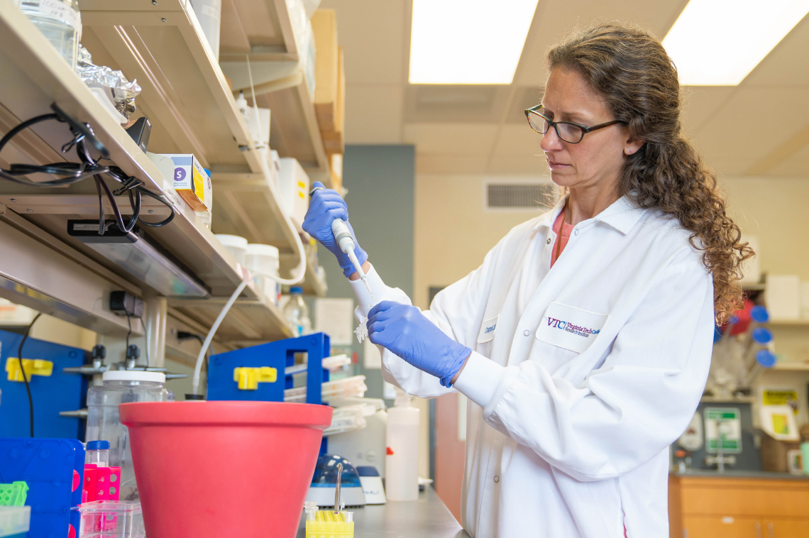 Lab setting with a female researcher injecting fluid into a container.