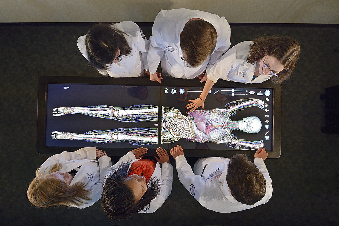 Aerial view of an Anatomage Table surrounded by six students wearing white labcoats